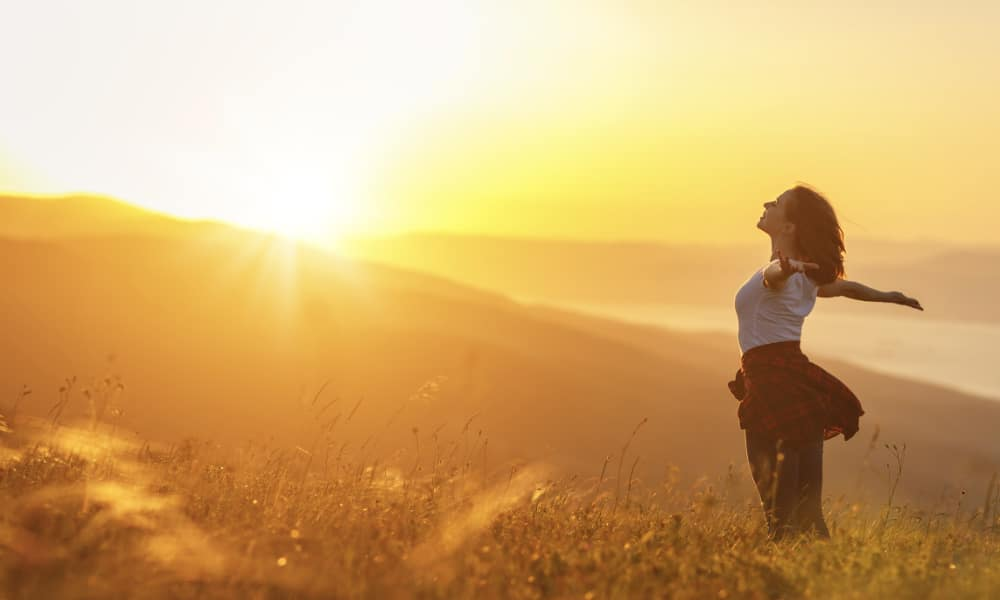 Happy woman with arms open facing sunset standing on mountain