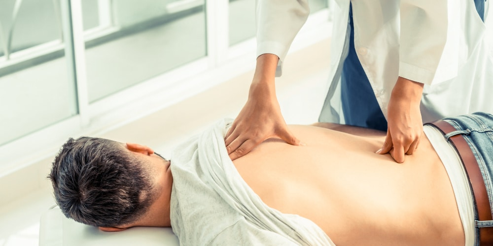 female chiropractor helping male patient