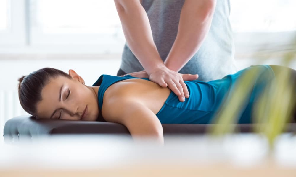 Chiropractor working with female patient