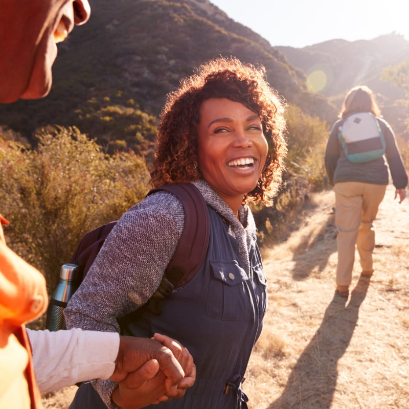 Happy woman holding hands of man while hiking