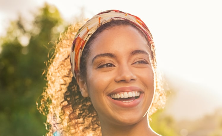 Young african woman smiling at sunset